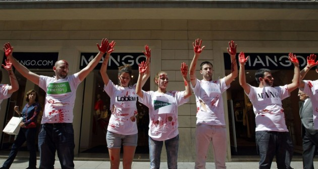 Activists of the Spanish trade union UGT (General Union of Workers) perform with fake blood in front of a Mango store in Barcelona on May 7 during a protest after the tragic death of hundreds of Bangladeshi workers who made clothes for western brands in precarious conditions. Photo: AFP